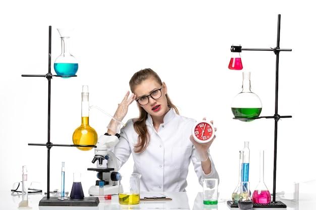 白い机の上の時計を保持している白い医療スーツの正面図女性医師ウイルスcovid化学パンデミック