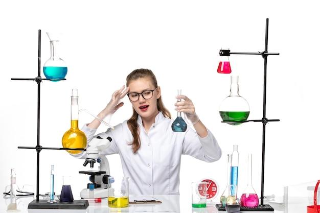 흰색 배경 바이러스 covid 유행성 코로나 바이러스에 솔루션 플라스크를 들고 흰색 의료 소송에서 전면보기 여성 의사