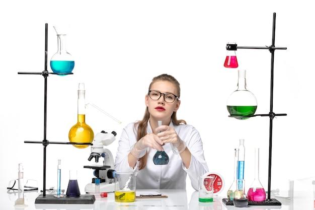 흰색 책상 바이러스 covid 유행성 코로나 바이러스에 솔루션 플라스크를 들고 흰색 의료 소송에서 전면보기 여성 의사