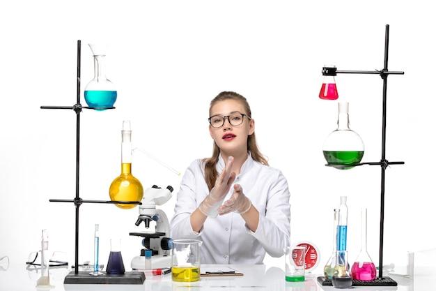 흰색 의료 소송에서 전면보기 여성 의사가 앉아 흰색 책상 바이러스 covid 유행성 코로나 바이러스에 대한 솔루션 작업