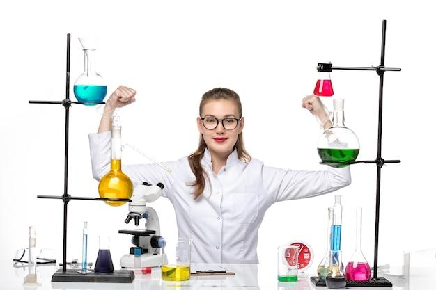 흰색 배경 Covid 화학 바이러스 유행병에 Flexing 솔루션 테이블 앞에 앉아 흰색 의료 정장에 전면보기 여성 의사 무료 사진