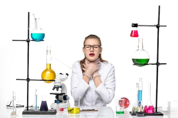 흰색 배경에 호흡 문제가있는 솔루션으로 테이블 앞에 앉아 흰색 의료 소송에서 전면보기 여성 의사 바이러스 covid 유행성 화학