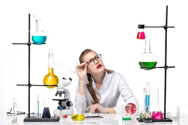 흰색 배경 바이러스 건강 covid 유행성 화학에 솔루션 테이블 앞에 앉아 흰색 의료 소송에서 전면보기 여성 의사