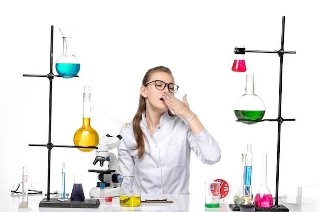 テーブルの前に座っている白い医療スーツを着た女性医師の正面図白い床にあくびをしているソリューションcovid化学ウイルスパンデミック