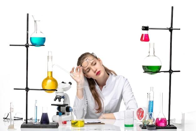 솔루션과 함께 앉아 흰색 배경 화학 유행성 바이러스 covid에 피곤한 느낌 흰색 의료 소송에서 전면보기 여성 의사