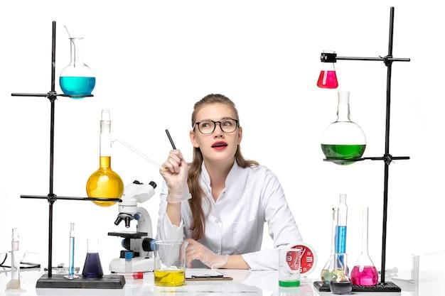 白い背景ウイルスcovidパンデミックコロナウイルスに書いているソリューションと座っている白い医療スーツの正面図の女性医師