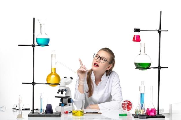 Вид спереди женщина-врач в белом медицинском костюме, сидящая с растворами на светлом белом фоне, вирусное здоровье, пандемия химии covid