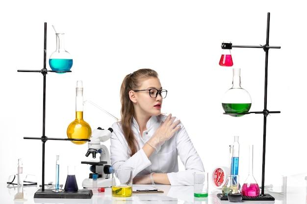밝은 흰색 배경에 솔루션과 함께 앉아 흰색 의료 소송에서 전면보기 여성 의사 바이러스 화학 전염병 covid