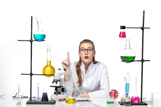 흰색 책상 바이러스 건강 covid 유행성 화학에 솔루션과 함께 앉아 흰색 의료 소송에서 전면보기 여성 의사