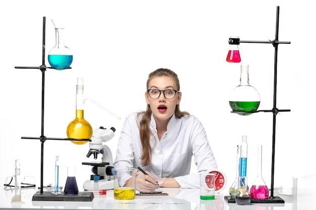 흰색 배경 바이러스 covid 유행성 코로나 바이러스에 작성하는 솔루션과 함께 앉아 흰색 의료 소송에서 전면보기 여성 의사