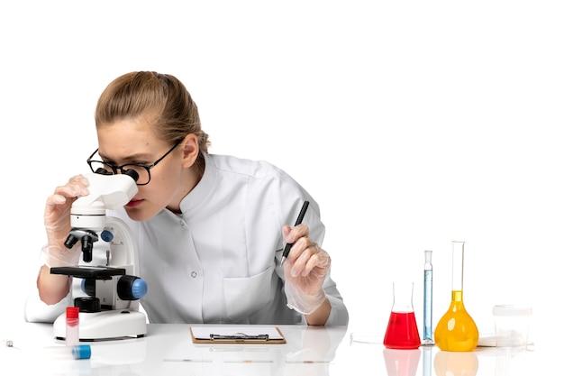 공백에 현미경을 사용하여 흰색 의료 소송에서 전면보기 여성 의사