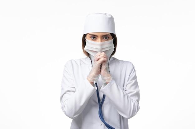 흰 벽에 유행성 포즈로 인해 마스크가있는 흰색 의료 소송에서 전면보기 여성 의사 의학 유행성 바이러스 covid-