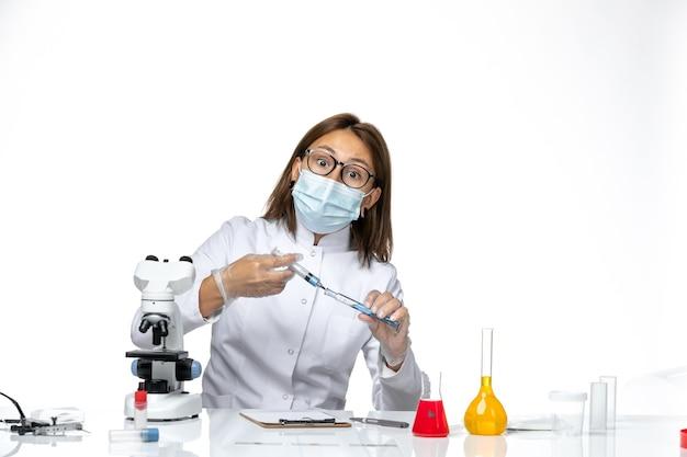 真っ白な空間に注射を保持しているため、マスク付きの白い医療スーツを着た女性医師の正面図