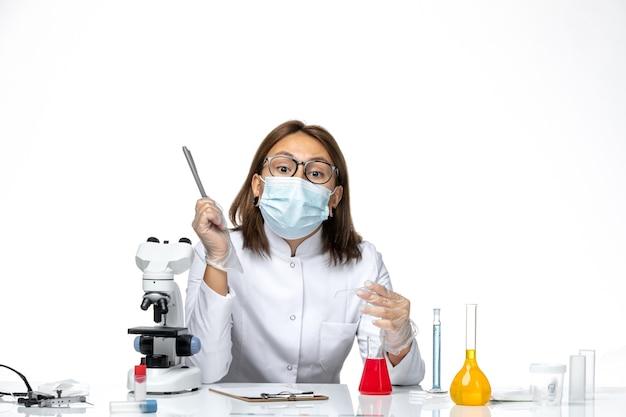 明るい白いスペースにcovidのため、マスク付きの白い医療スーツの正面図の女性医師