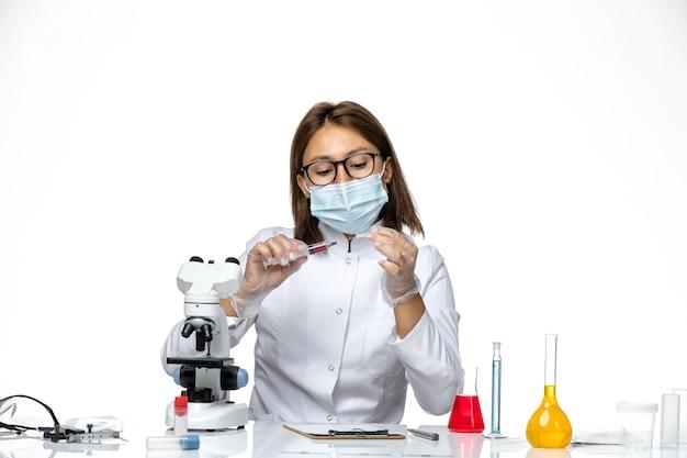 明るい白色のスペースに注射を使用してcovidによるマスク付きの白い医療スーツの正面図の女性医師