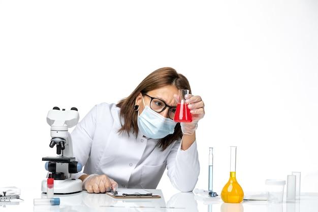 明るい白いスペースでソリューションを共同作業するため、マスク付きの白い医療スーツの正面図の女性医師