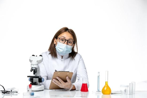 Covid 공백에 뭔가 쓰는 때문에 마스크와 흰색 의료 소송에서 전면보기 여성 의사