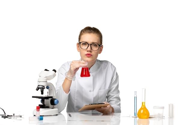 明るい白いスペースでソリューションを扱う白い医療スーツの正面図の女性医師