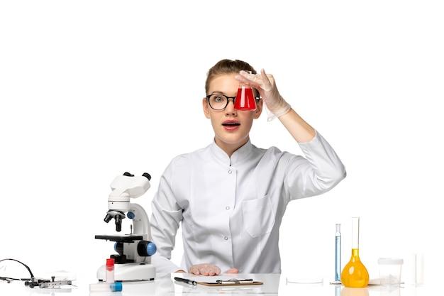 Вид спереди женщина-врач в белом медицинском костюме, работающая с растворами на белом столе