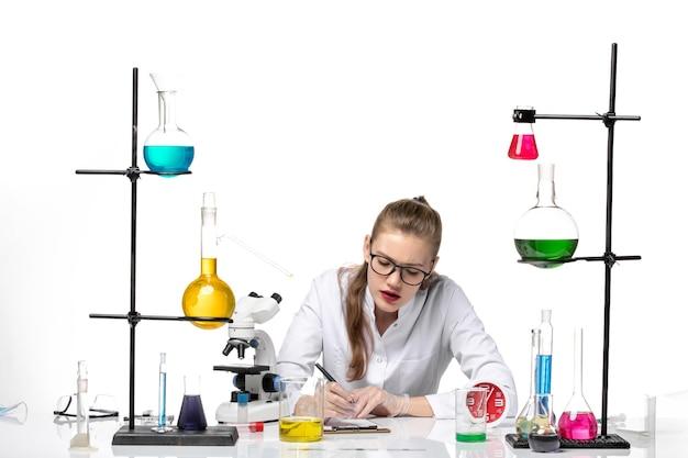 흰색 배경에 바이러스 건강 covid 유행성 화학에 뭔가 쓰는 흰색 의료 소송에서 전면보기 여성 의사