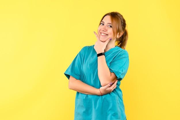 黄色い空間に微笑んでいる正面図の女医