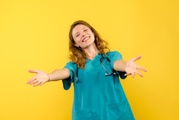Vista frontale del medico femminile che sorride appena sulla parete gialla