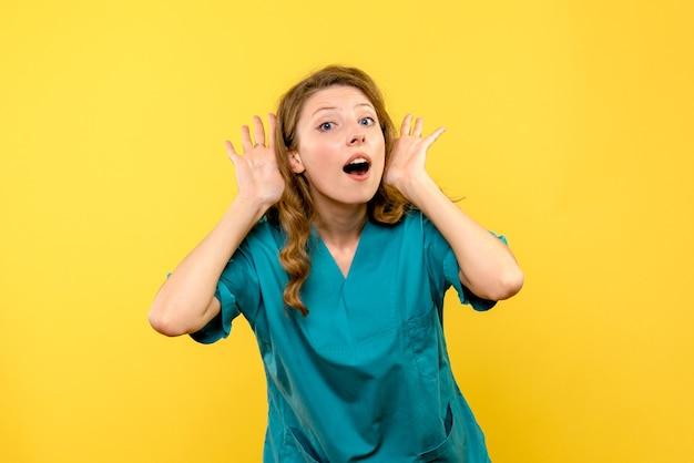 Vista frontale del medico femminile che ascolta sulla parete gialla