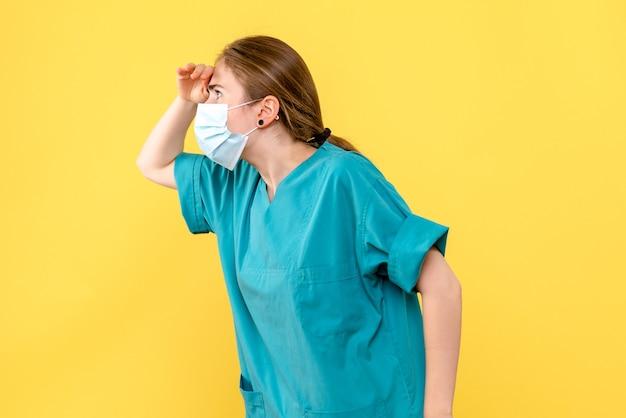 黄色の背景パンデミックcovid健康ウイルスの距離を見ている正面図の女性医師
