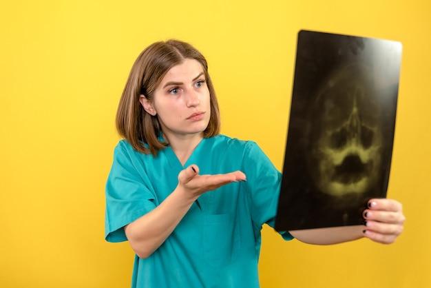 黄色の空間でx線を見て正面図の女性医師