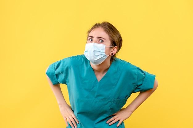 黄色の背景の健康病院のcovidパンデミックを不思議そうに見ている正面図の女性医師