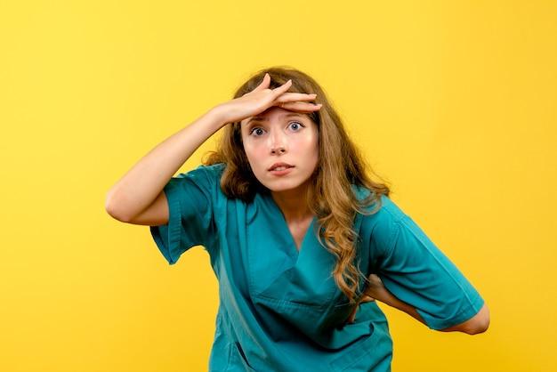 Vista frontale della dottoressa guardando la distanza sulla parete gialla