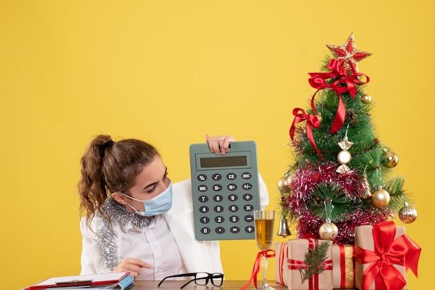 Medico femminile di vista frontale nel calcolatore della holding della maschera