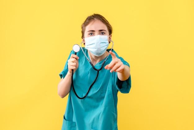 Medico femminile di vista frontale in maschera su covid pandemia di virus di salute di sfondo giallo chiaro