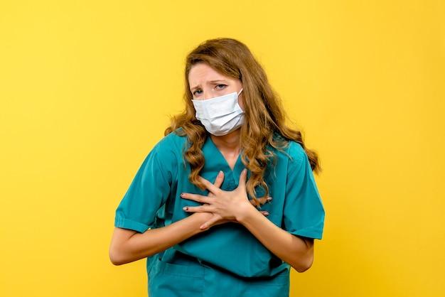 Medico femminile di vista frontale in maschera sullo spazio giallo chiaro