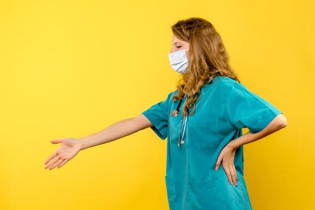 Vista frontale della dottoressa in maschera che agitano le mani sulla parete gialla