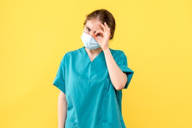 Medico femminile di vista frontale in maschera sulla pandemia di covid dell'ospedale di salute del fondo giallo