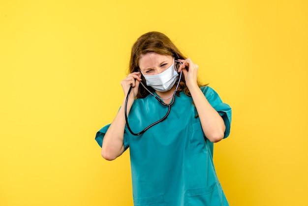 Vista frontale della dottoressa in maschera sulla salute del medico dell'ospedale del pavimento giallo