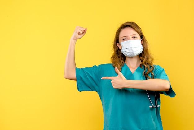 Vista frontale della dottoressa in maschera sulla parete gialla