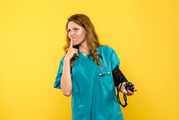 Vista frontale del medico femminile che misura la pressione sul muro giallo chiaro