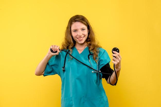 노란색 공간에 압력을 측정하는 전면보기 여성 의사