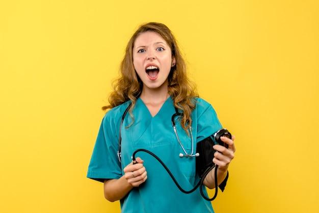 Вид спереди женщина-врач, измеряющая давление на желтом пространстве