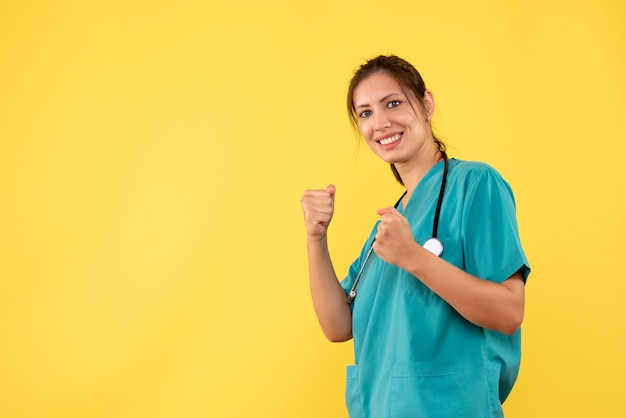 Front view female doctor in medical shirt in boxing stand on yellow background