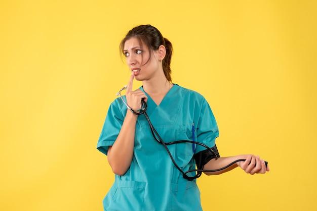 Medico femminile di vista frontale in camicia medica che controlla la sua pressione su priorità bassa gialla