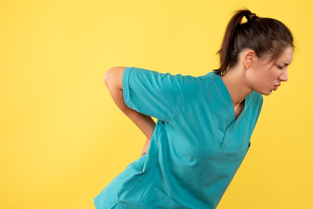 Front view female doctor in medical shirt having back pain on yellow background
