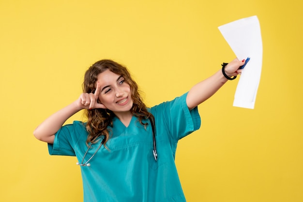 Front view female doctor in medical shirt holding analysis, uniform covid-19 health emotion pandemic virus