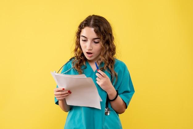 Medico femminile di vista frontale in camicia medica che tiene analisi, virus pandemico di emozioni di salute covid-19 uniforme