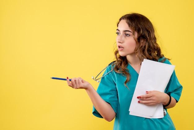 Medico femminile di vista frontale nell'analisi medica della tenuta della camicia, emozione uniforme del virus pandemico di salute covid-19