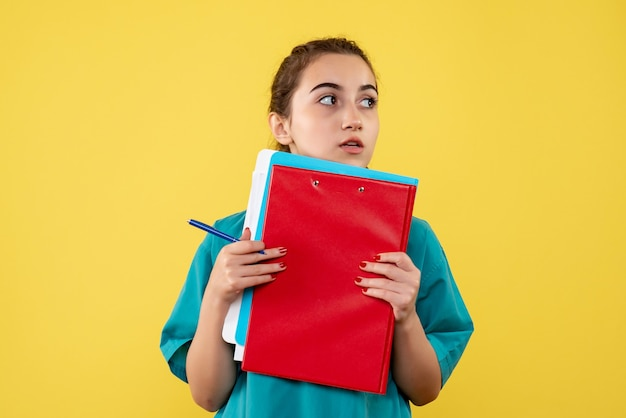 Medico femminile di vista frontale in camicia medica che tiene note differenti, uniforme covid-19 di emozione di salute di virus pandemico di colore