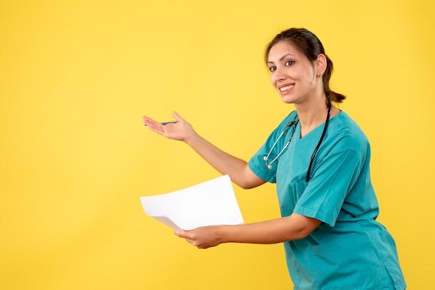Medico femminile di vista frontale in camicia medica che tiene analisi della carta su fondo giallo