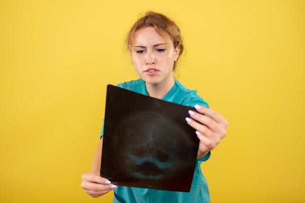 Medico femminile di vista frontale in camicia medica che tiene i raggi x, virus pandemico di emozione di salute di colore covid-19